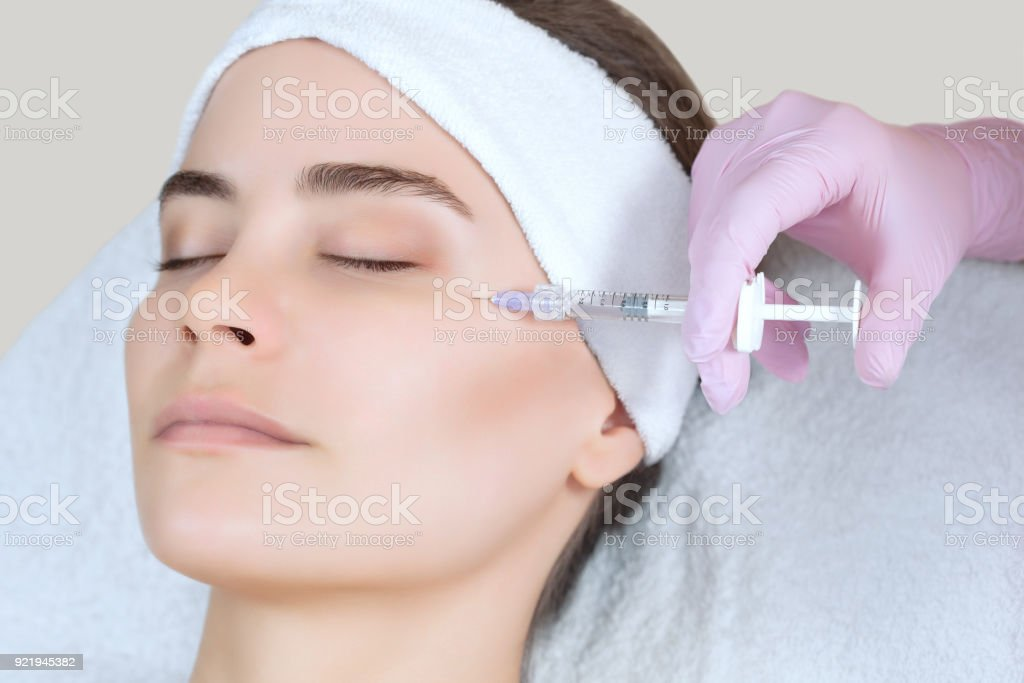 The doctor cosmetologist makes the Rejuvenating facial injections procedure for tightening and smoothing wrinkles on the face skin of a beautiful, young woman stock photo