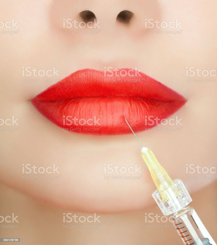The doctor cosmetologist makes the Rejuvenating injections on the lips of a beautiful, young woman. stock photo