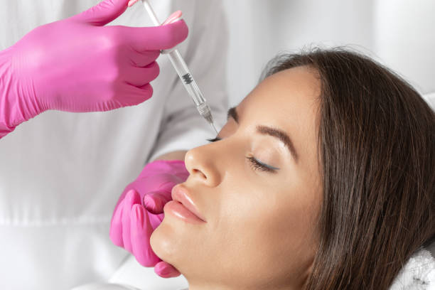 The doctor does injections to correct the hump on the nose with the beauty of the blonde. The beautician doees injections against wrinkles on the face. Women's cosmetology in a beauty salon. stock photo