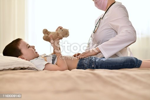 istock The doctor examines the baby tummy with a bear. 1163009140