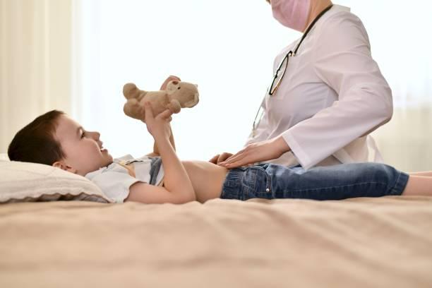 o médico examina a barriga do bebê com um urso. - apendicite - fotografias e filmes do acervo