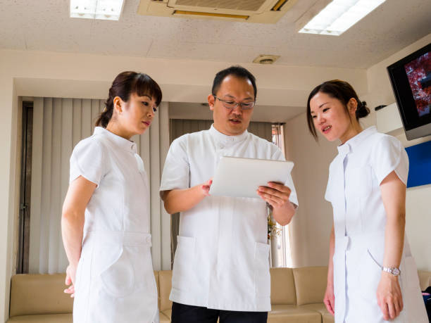 The doctor explains to the nurses to use  the memo pad. stock photo