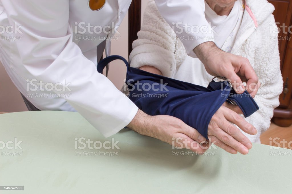 The doctor in a white coat put a sling on the hand of a very old woman. stock photo