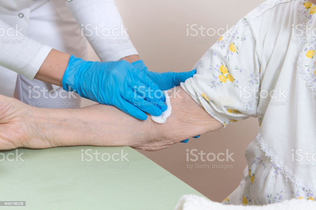 The doctor in disposable gloves holds the hand and forearm of an old woman in a nightgown. stock photo