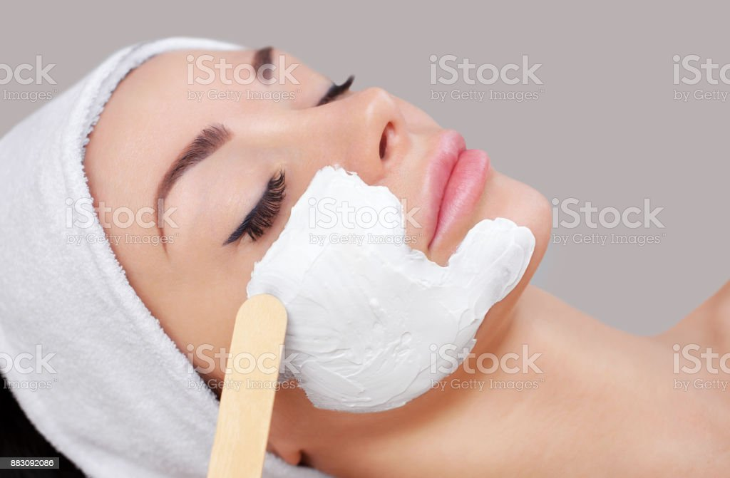 The doctor is a cosmetologist for the procedure of cleansing and moisturizing the skin, applying a mask with stick to the face of a young woman in beauty salon stock photo