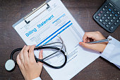 istock The doctor is calculating the cost and signing the name 1216819352