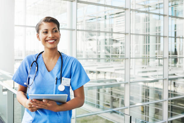 The doctor is in Portrait of a confident young doctor holding a digital tablet in a modern hospital looking away stock pictures, royalty-free photos & images