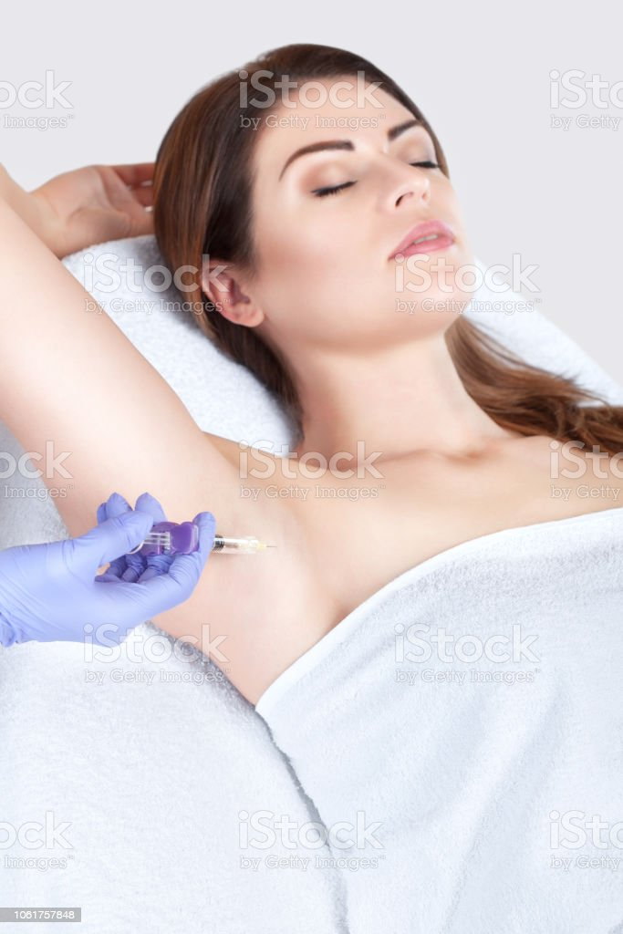 The doctor makes intramuscular injections of botulinum toxin in the underarm area stock photo