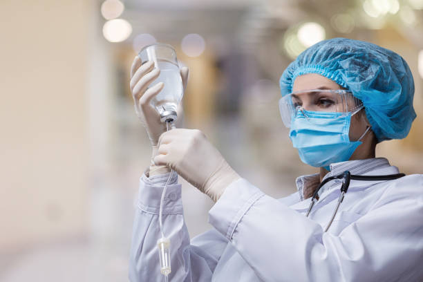 The doctor prepares a system for transfusion of infusion solutions . The doctor prepares a system for transfusion of infusion solutions on a blurred background. infused stock pictures, royalty-free photos & images