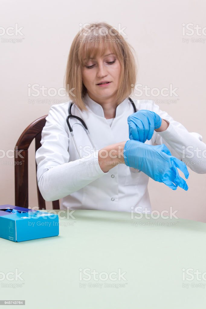 The doctor sits at the table and prepares herself for examination, she puts on her blue latex medical gloves stock photo