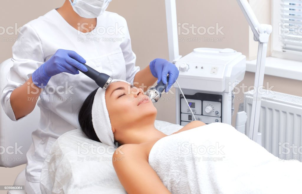 The doctor-cosmetologist makes the procedure an ultrasonic cleaning of the facial skin of a beautiful, young woman in a beauty salon stock photo