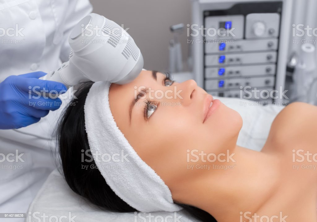 The doctor-cosmetologist makes the procedure Cryotherapy of the facial skin of a beautiful, young woman stock photo