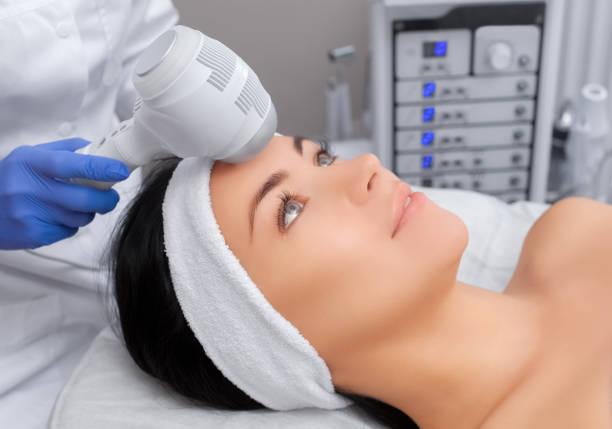 il medico-cosmetologo effettua la procedura crioterapia della pelle del viso di una bella, giovane donna - crioterapia foto e immagini stock