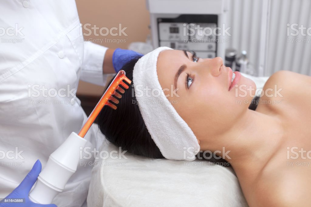 The doctor-cosmetologist makes the procedure Microcurrent therapy On the hair of a beautiful, young woman in a beauty salon. stock photo