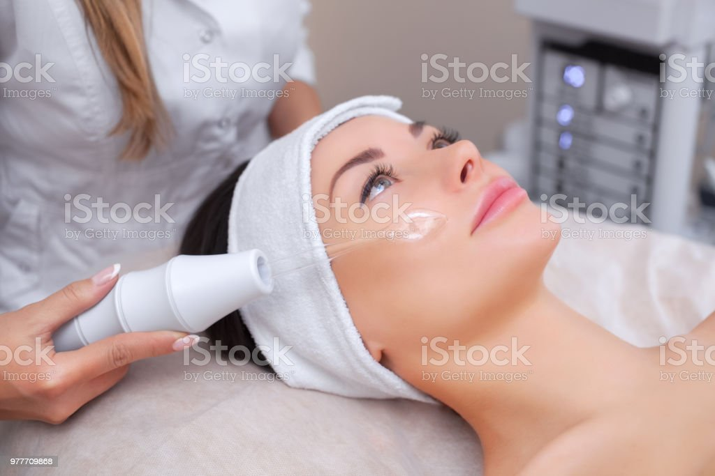 The doctor-cosmetologist makes the procedure Microcurrent therapy stock photo