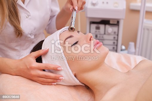 istock The doctor-cosmetologist makes the procedure Microdermabrasion of the facial skin of a beautiful, young woman 690529646