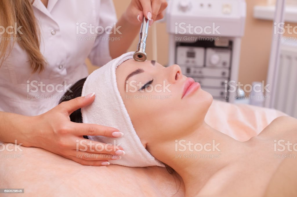 The doctor-cosmetologist makes the procedure Microdermabrasion of the facial skin of a beautiful, young woman stock photo