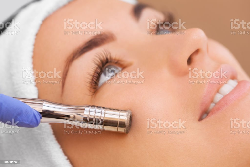 The doctor-cosmetologist makes the procedure Microdermabrasion of the facial skin of a beautiful, young woman in a beauty salon. stock photo