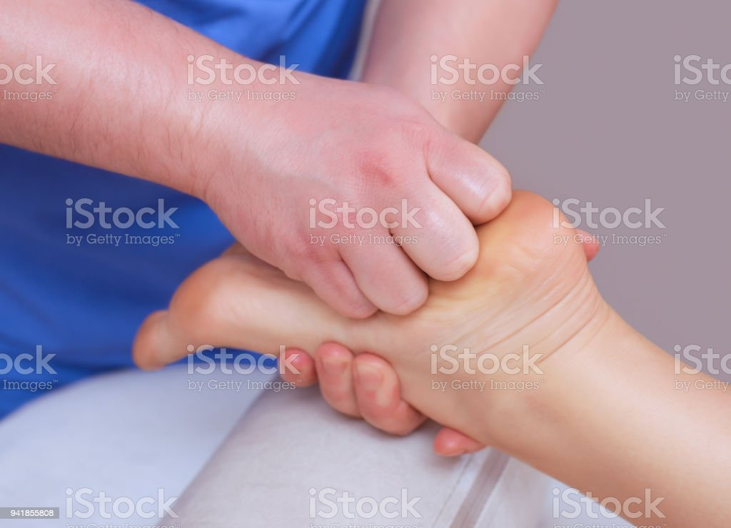 The doctor-podiatrist does an examination and massage of the patient's foot stock photo