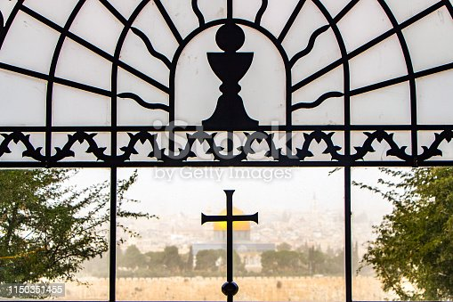 A landscape photo that focuses on The Dome of the Rock as viewed through a church window on the Mount of Olives