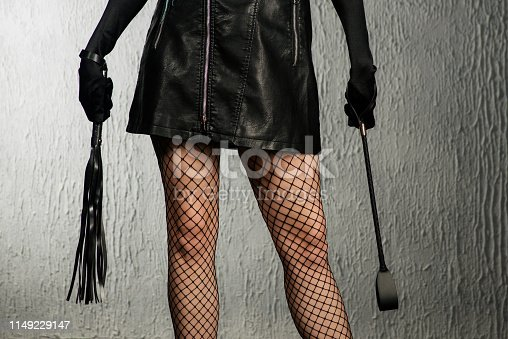 istock The dominant woman in a leather dress with a stack and a whip in her hand. Bdsm outfit 1149229147