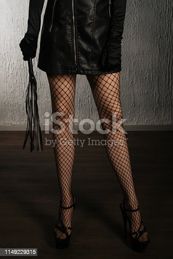 istock The dominant woman in a leather dress with a whip in her hand. Bdsm outfit 1149229315