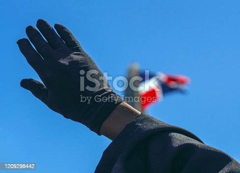 istock The Dominican flag with a black glove in front 1209298442