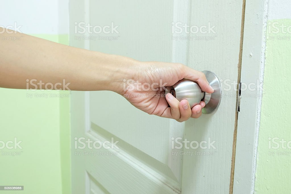 the door knob is turned by one hand stock photo