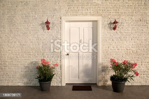 istock The door of the house and the flowers in front of the door. White stone wall, pink flowers and trees 1309726171
