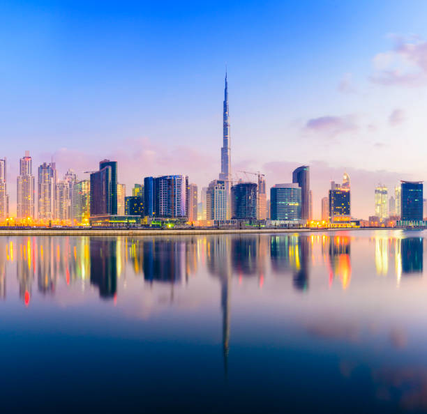 The Downtown Dubai City Skyline at Sunset Illuminated Reflection in the Still Lagoon Waters burj khalifa stock pictures, royalty-free photos & images