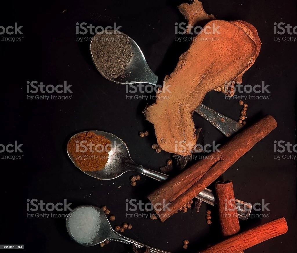 The dried chilli powder in old stainless steel spoon was put at the middle of the spoon of suger and the spoon of pepper powder,plenty of Chinese herbs around,on black background,in abstract art design,vintage and art style. stock photo