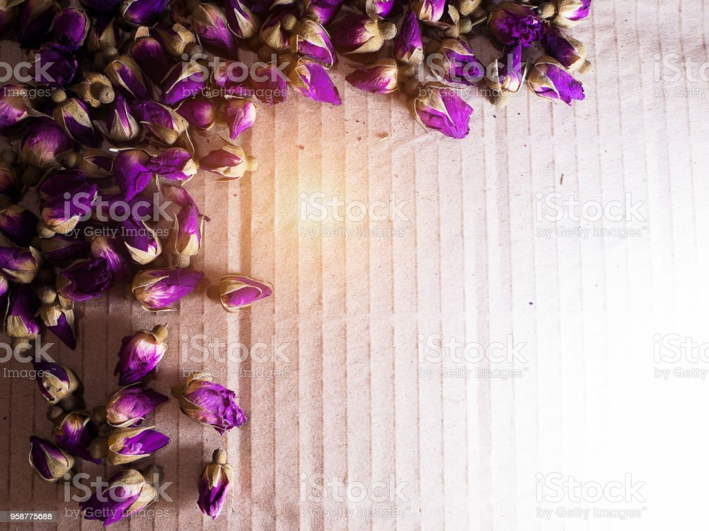 The dried roses plenty on brown background with wooden spoon,vintage and art style stock photo