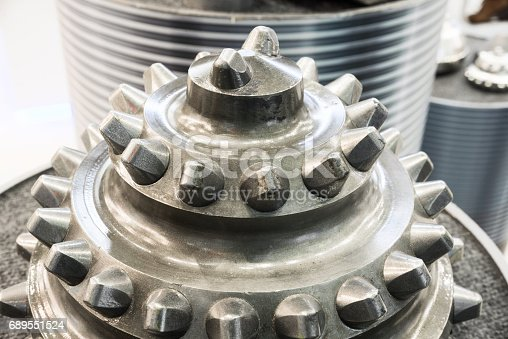 The drill bit, shot close-up with shallow depth of field. Industrial background.