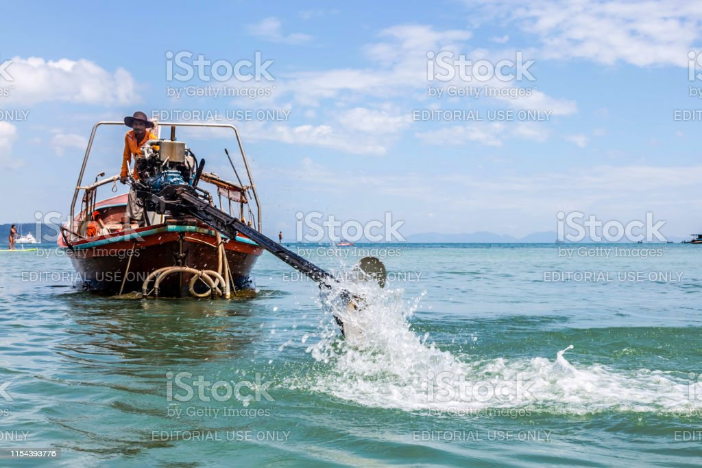 The driver of a longtail motorboat drives a motor with a long drive...