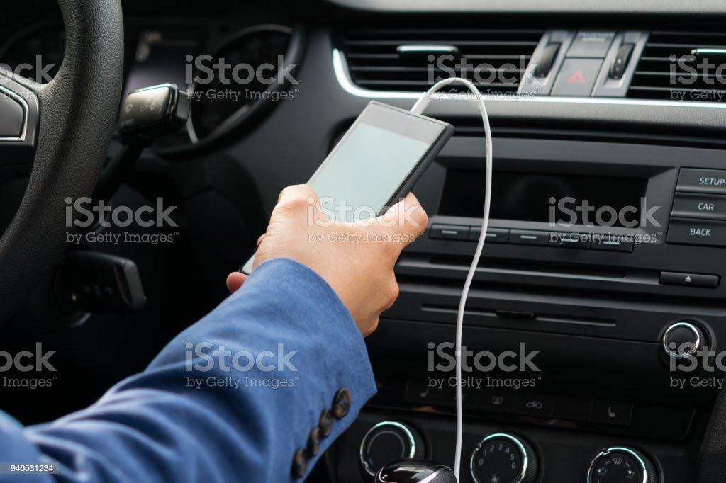 el conductor del vehículo, sostiene en su mano el teléfono conectado por un cable blanco, sistema de música del coche - Foto de stock de Adaptador libre de derechos