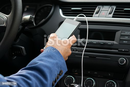 istock the driver of the vehicle, holds in his hand the phone connected by a white wire, to the car's music system 946531234