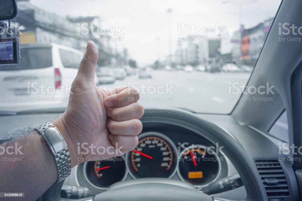The driver raised his thumb while driving on the road. stock photo