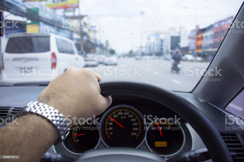 The driver used left hand to drive on the road. stock photo