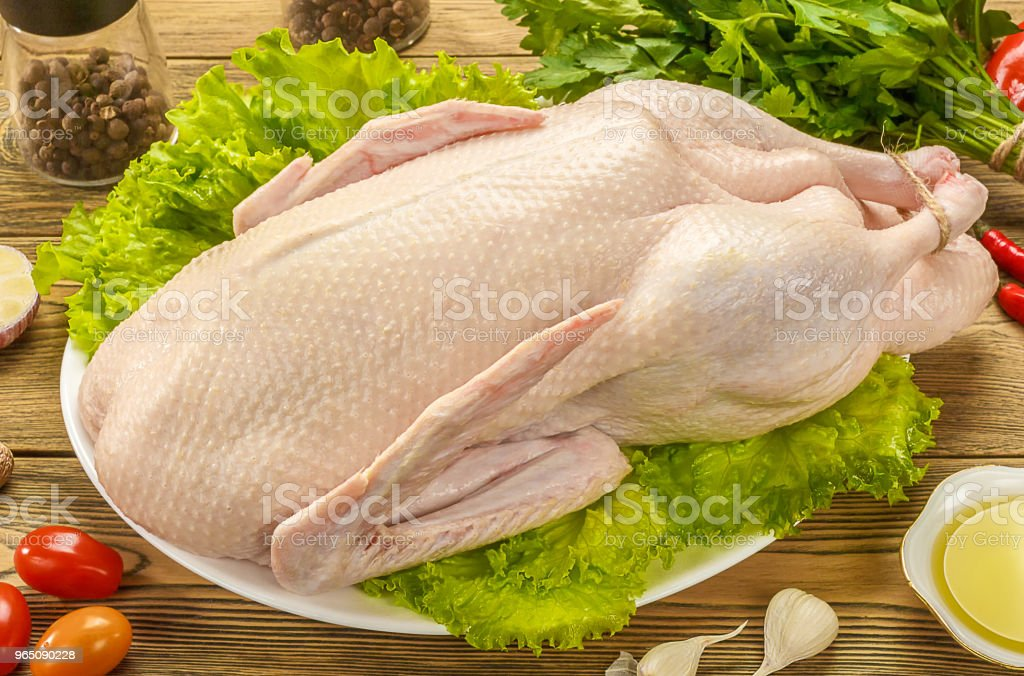 The duck is raw, ready to cook. Gutted carcass of a bird. Wooden table. Recipe preparations. Dietary food. Health food. Farm product. zbiór zdjęć royalty-free