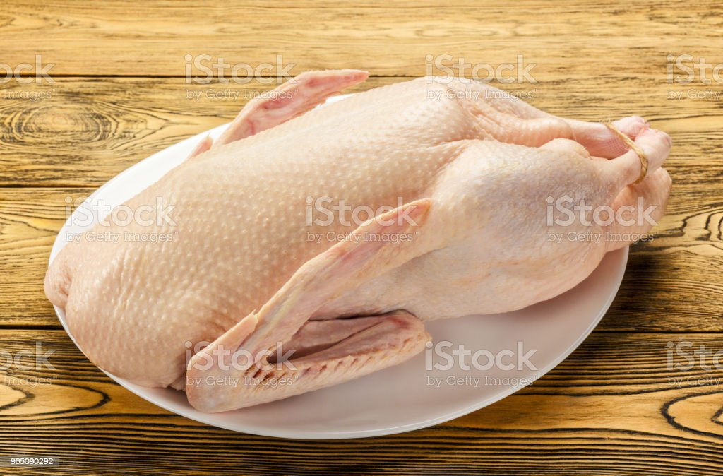 The duck is raw, ready to cook. Gutted carcass of a bird. Wooden table. Recipe preparations. Dietary food. Health food. Farm product. royalty-free stock photo