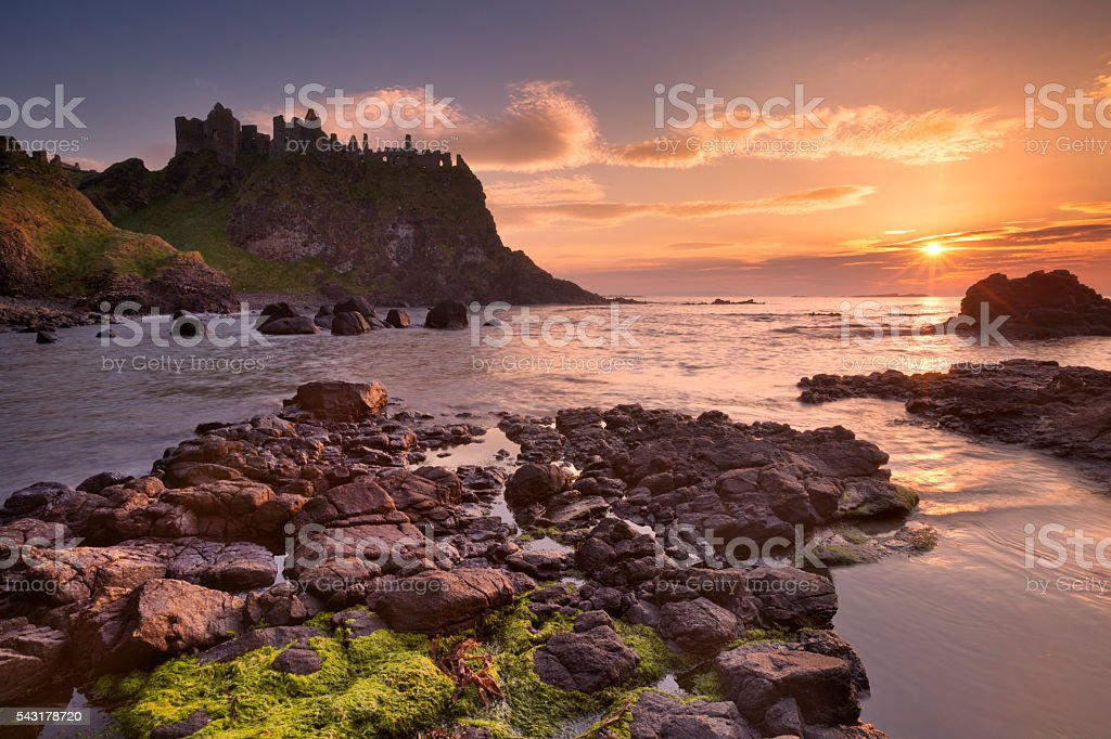 The Dunluce Castle in Northern Ireland at sunset stock photo