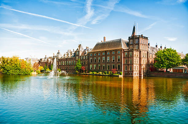 The Dutch Parliament in The Hague, Netherlands Binnenhof (Dutch Parliament), The Hague (Den Haag), The Netherlands. Visible are Historic buildings, art museum Mauritshuis along the pond Hofvijver, fountain and beautiful cloudscape over the reflection in the water. courtyard stock pictures, royalty-free photos & images