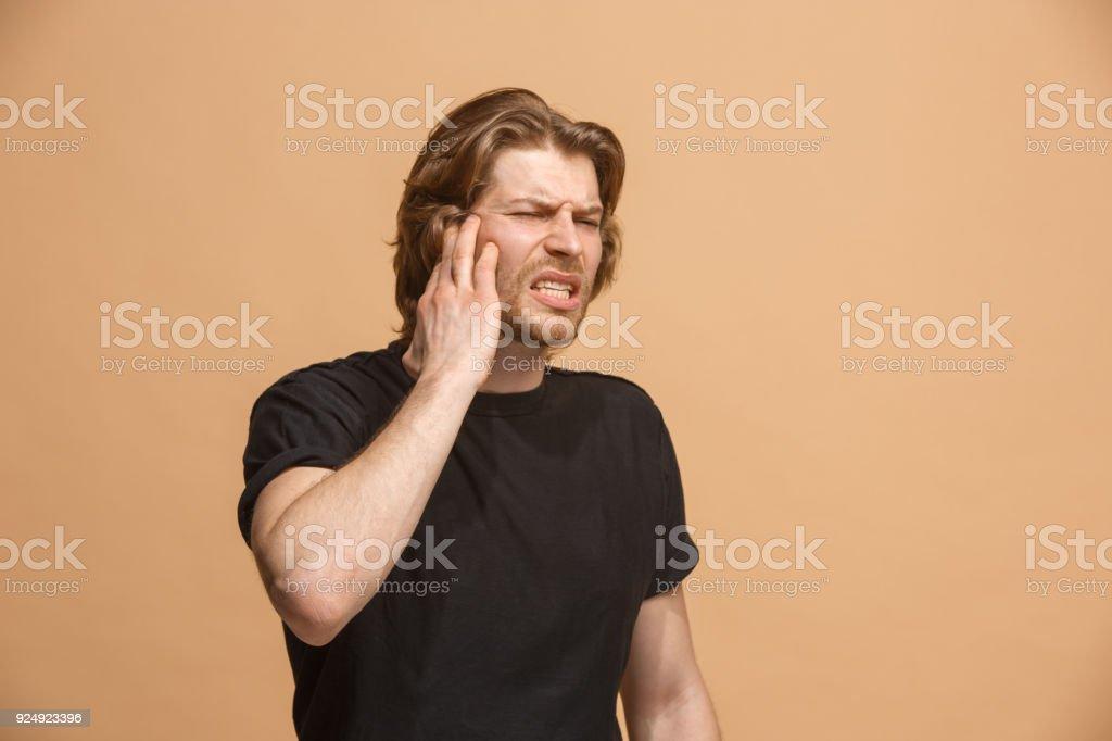 Sore ear. Ear ache concept. The sad crying man with headache or pain...