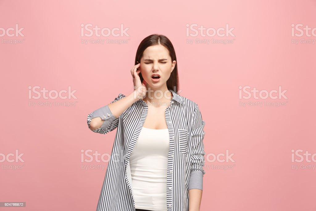 The Ear ache. The sad woman with headache or pain on a pink studio background stock photo