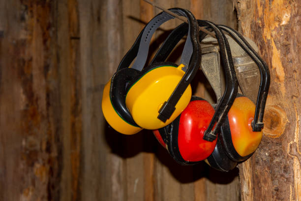 The ear muffs hang from a nail on the log wall. Village sawmill. Health protection stock photo