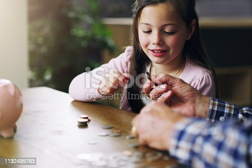 Shot of a little girl learning about money from her grandfather
