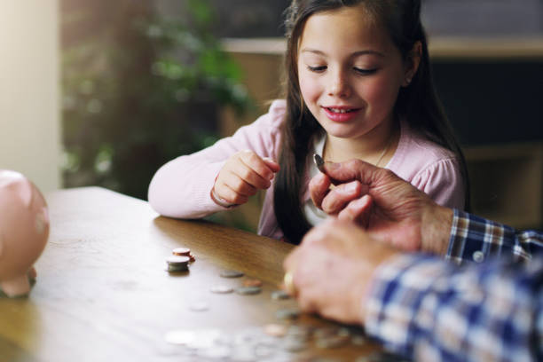 The earlier the better Shot of a little girl learning about money from her grandfather allowance stock pictures, royalty-free photos & images