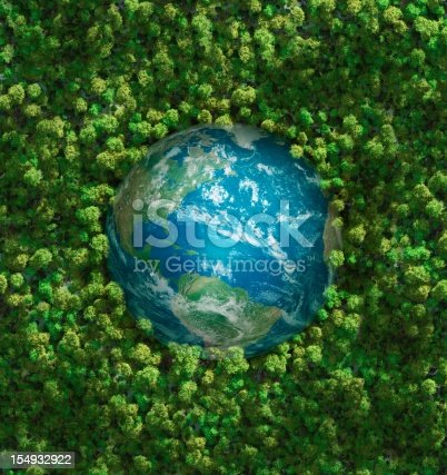 Ecology concept: aerial view of the earth surrounded by a  healthy forest. Computer generated. Subtle grain texture added. Earth's maps courtesy of http://www.shadedrelief.com