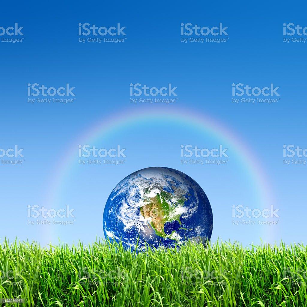 The earth on meadow with rainbow against a blue sky stock photo