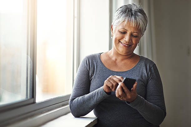 the easier way to connect to the things that matter - older woman phone stock photos and pictures